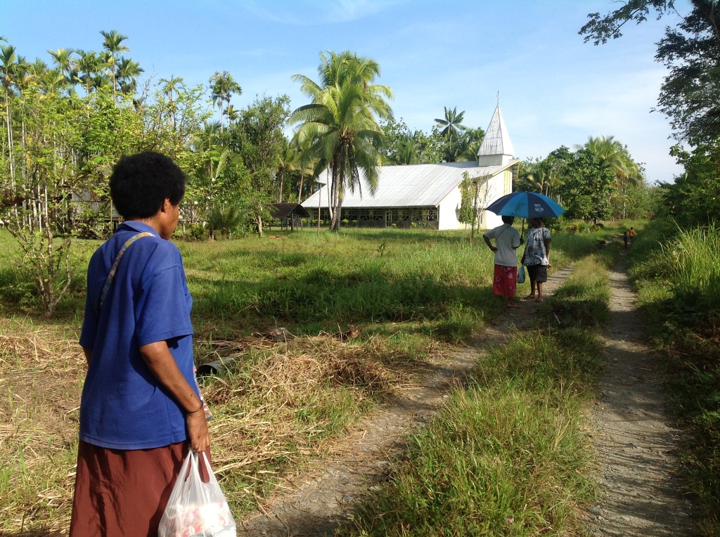 Sr Elizabeth walking through Arop village to the local Church